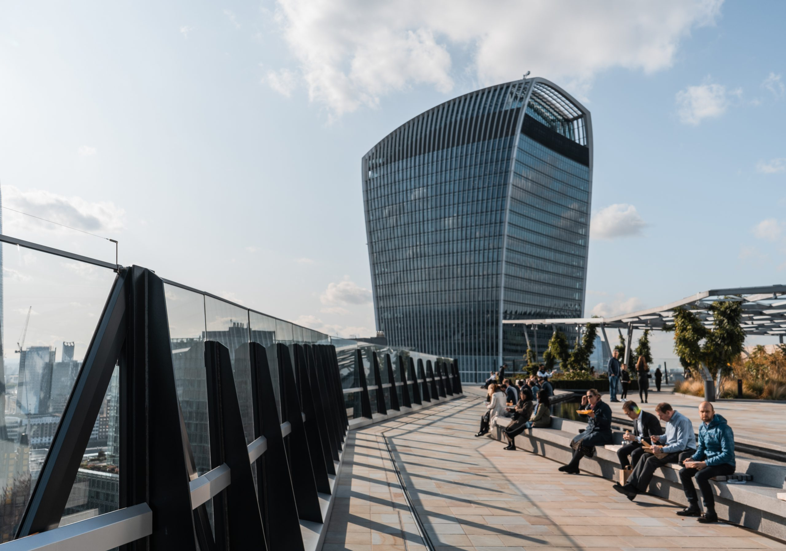 people sat down eating and enjoying one of the views in London from a fen court rooftop garden