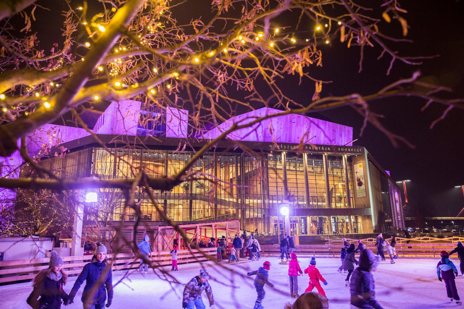 people skating on neon light lit outdoor ice rink