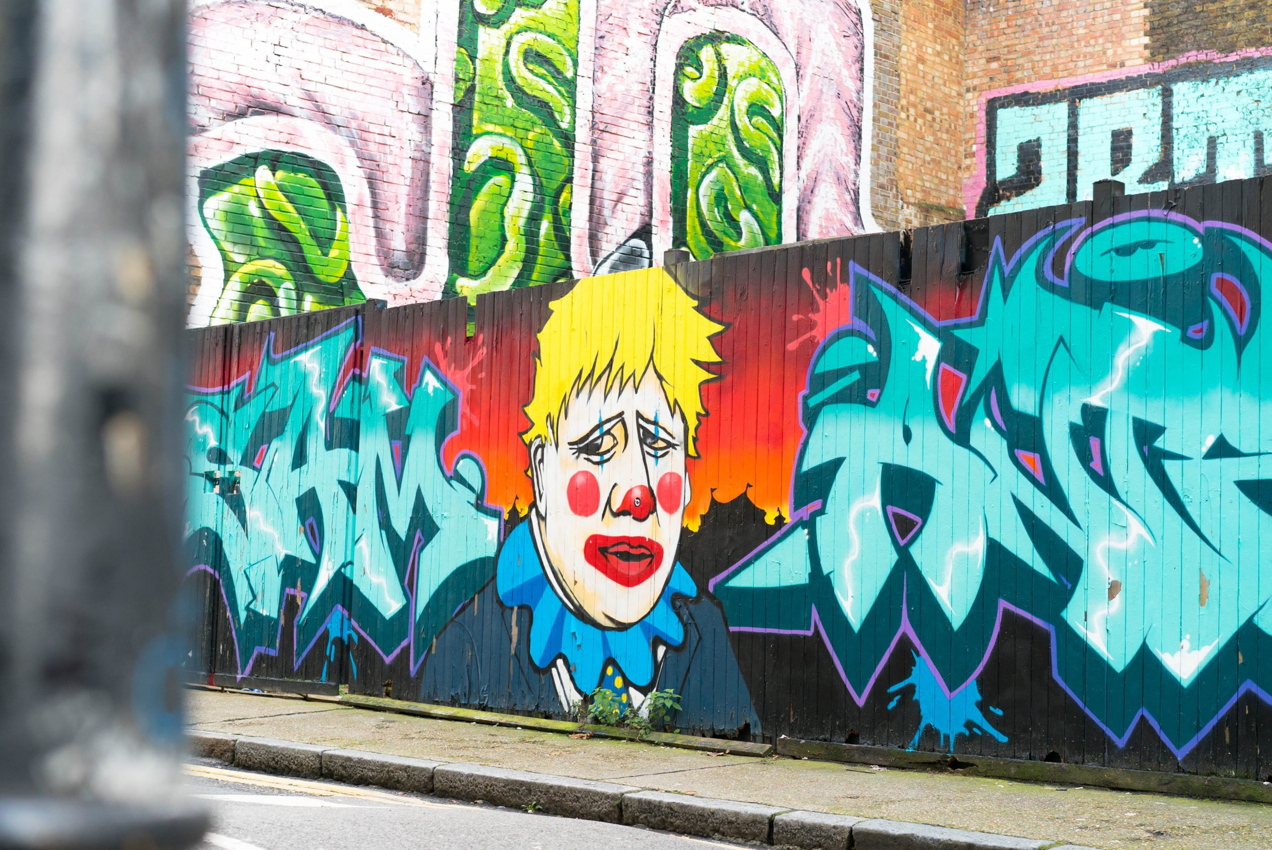 Street art in brick lane showing boris johnson as a clow with a white face red cheeks lipstick and yellow hair behind a orange and red burning city