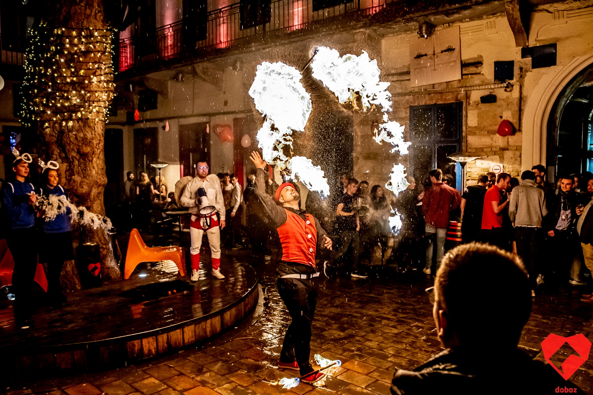 fire breather with read waistcoat stood in a dimly lit courtyard surrounded by people watching