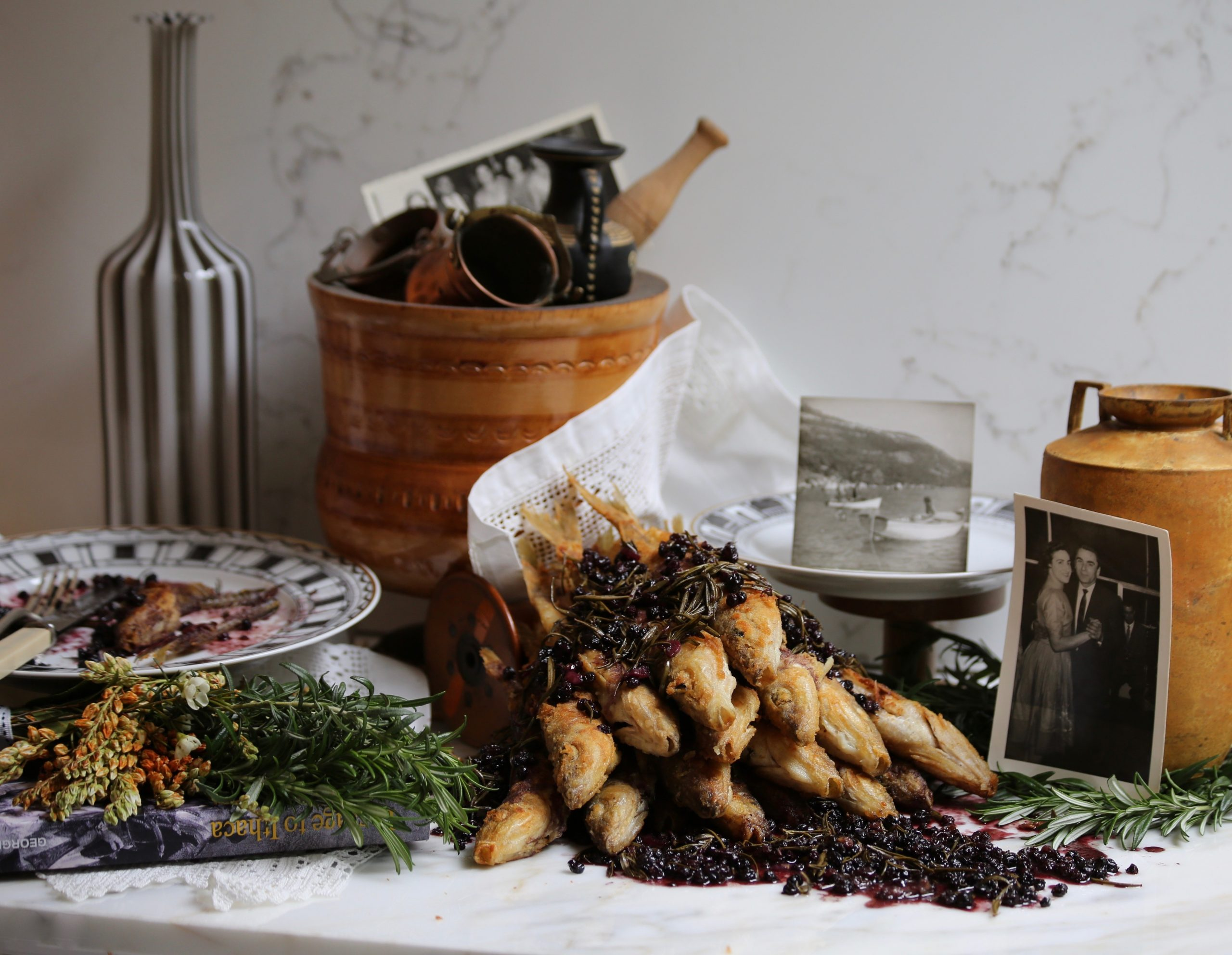 table with a pile neatly placed ithican savoro fish adorned with black berries next to various artefacts and photographs